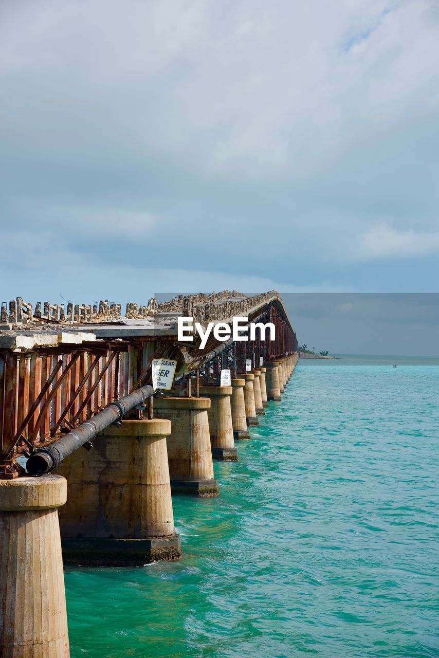 water, sky, sea, cloud - sky, architecture, built structure, nature, scenics - nature, day, waterfront, beauty in nature, wood - material, no people, tranquil scene, bridge, tranquility, horizon over water, pier, horizon, outdoors, turquoise colored, wooden post, long