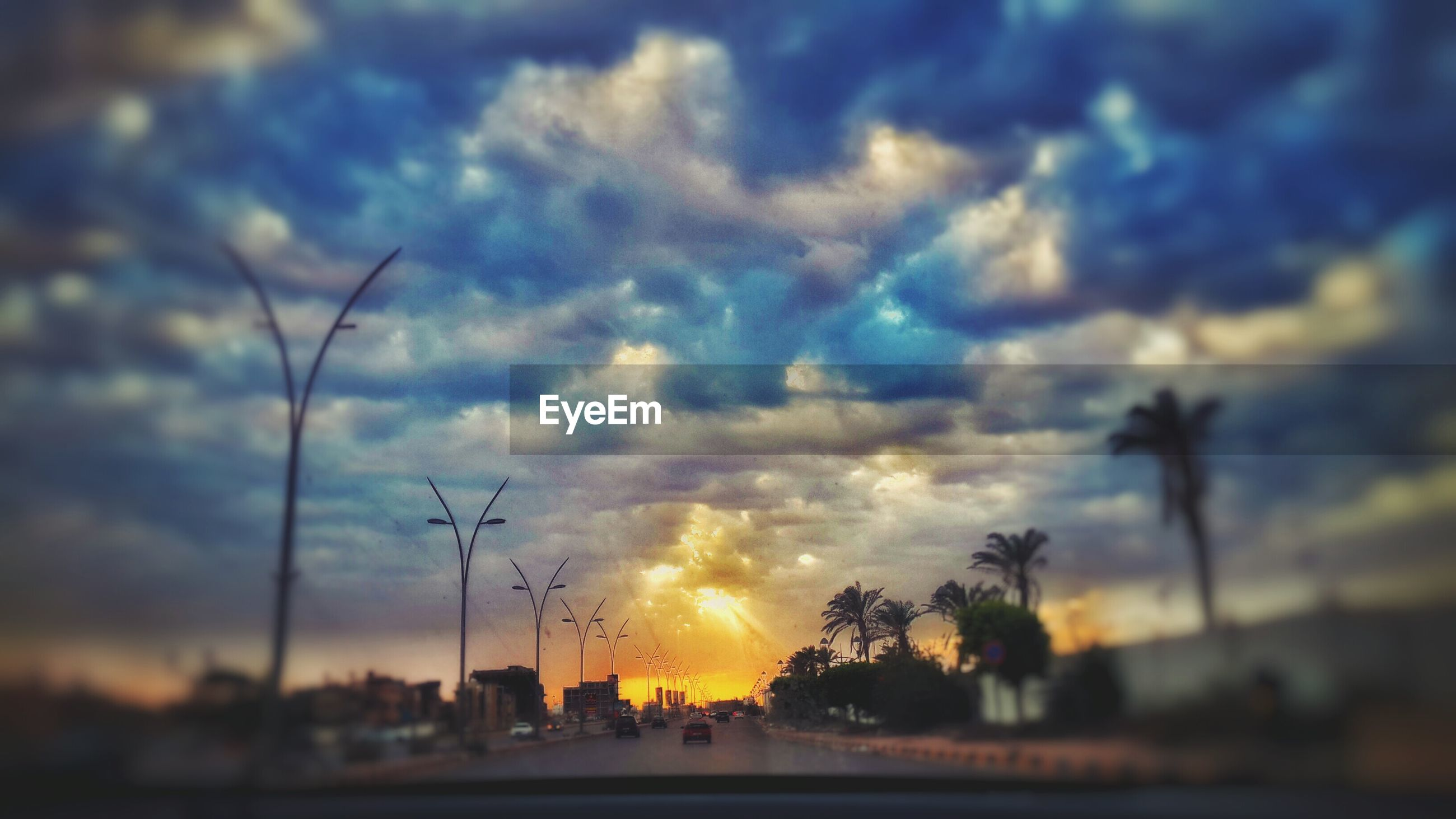 sunset, sky, cloud - sky, silhouette, tree, road, cloudy, beauty in nature, nature, orange color, cloud, transportation, tranquility, scenics, tranquil scene, street light, street, car, dramatic sky, outdoors