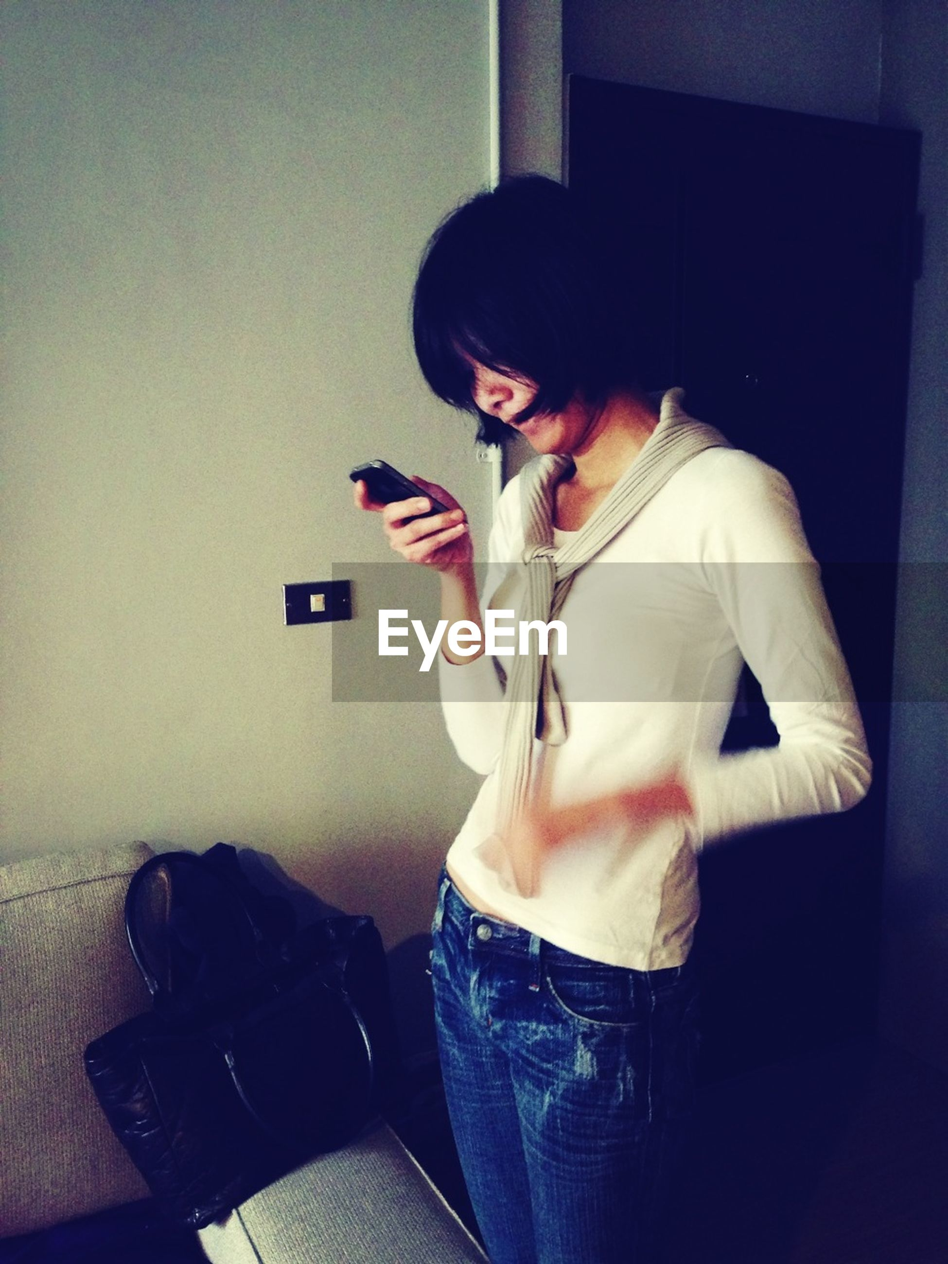 indoors, person, home interior, young adult, casual clothing, lifestyles, three quarter length, young women, front view, leisure activity, domestic room, holding, sitting, bed, full length, wireless technology, bedroom, wall - building feature