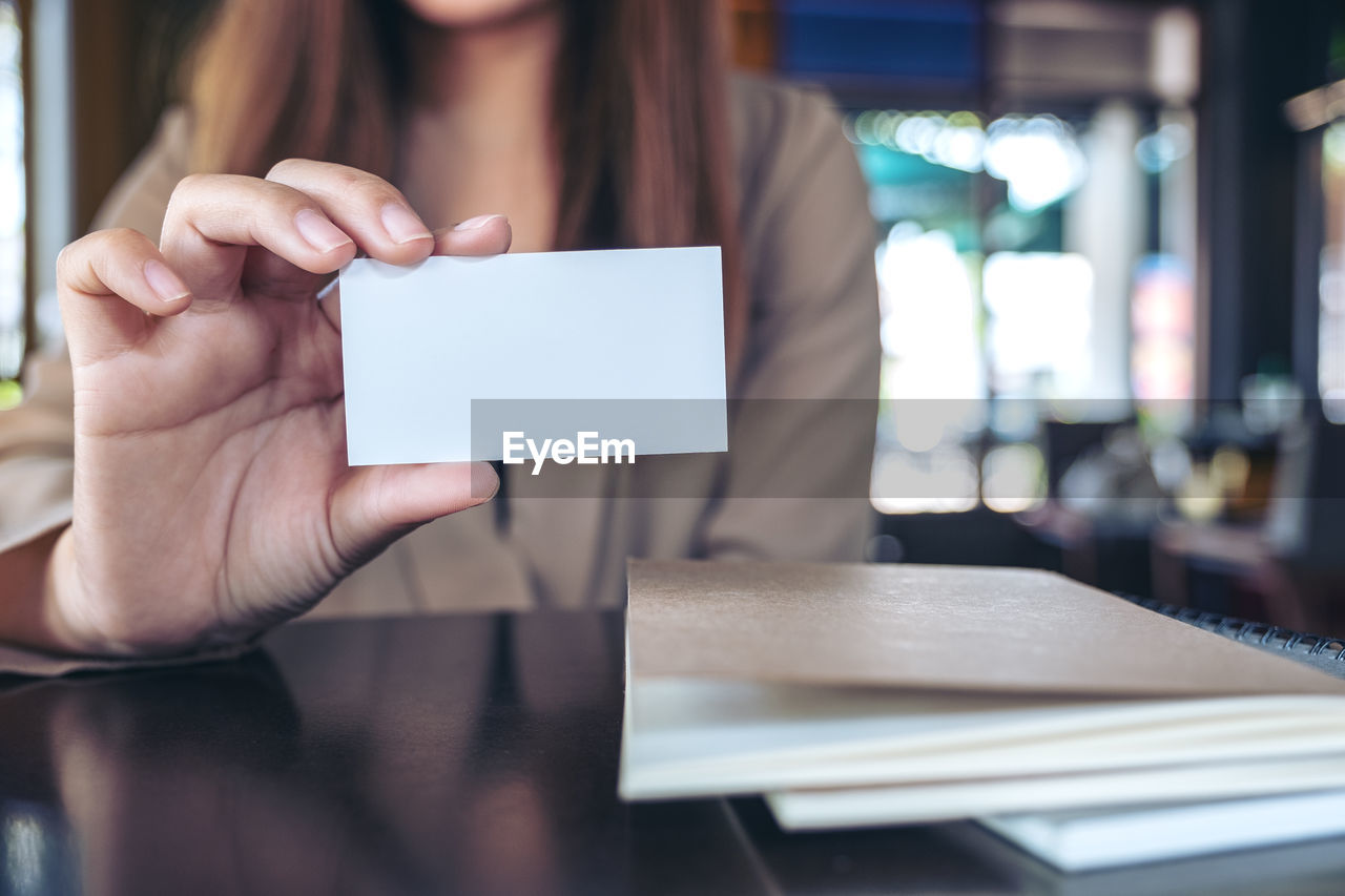 Midsection of businesswoman showing blank card at table in cafe