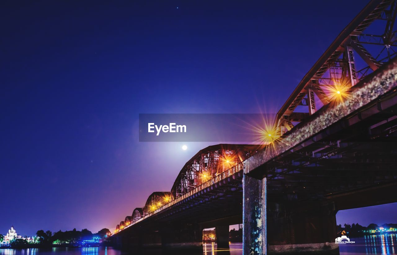 illuminated, architecture, night, sky, built structure, connection, bridge, bridge - man made structure, transportation, nature, engineering, low angle view, city, river, blue, copy space, clear sky, lighting equipment, building exterior, outdoors, light, architectural column, long