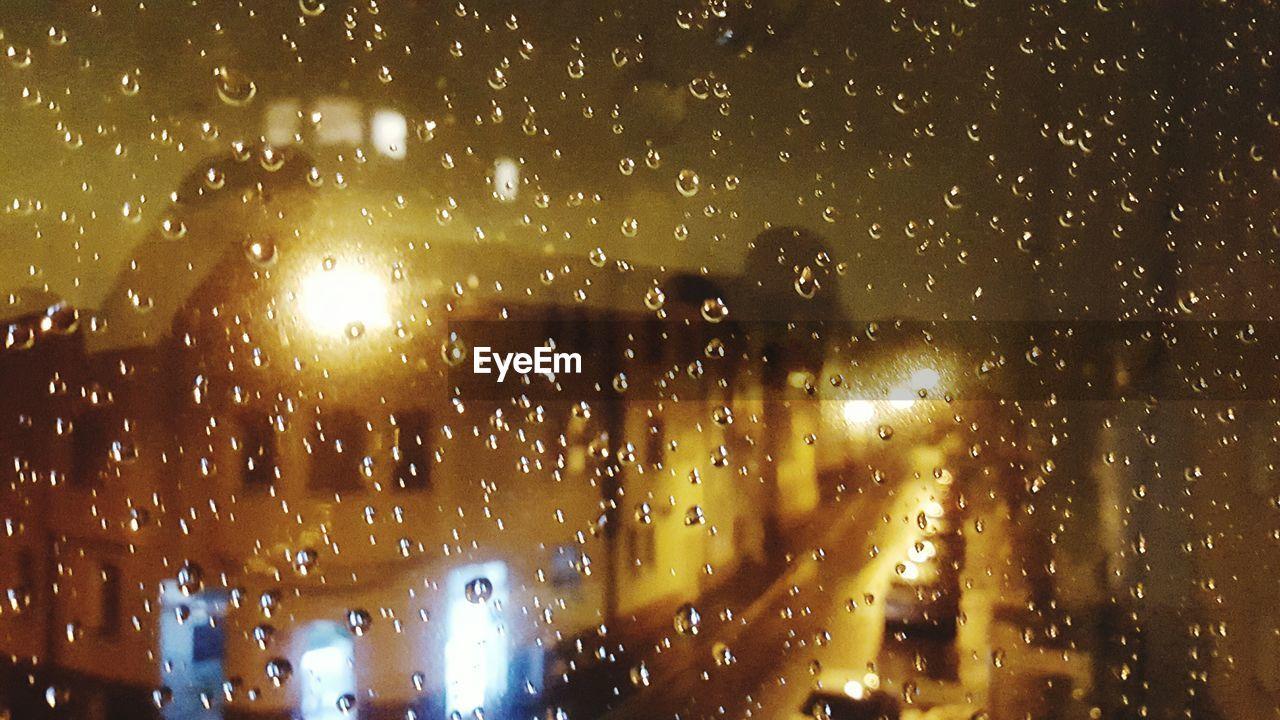 illuminated, wet, rain, drop, night, raindrop, rainy season, window, land vehicle, no people, car, water, windshield, indoors, close-up, architecture, sky, nature, city