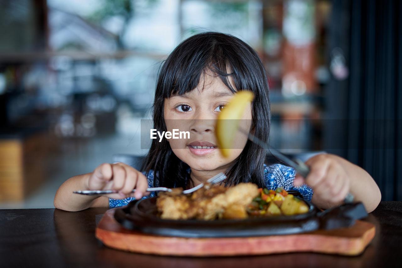 Portrait of girl eating food