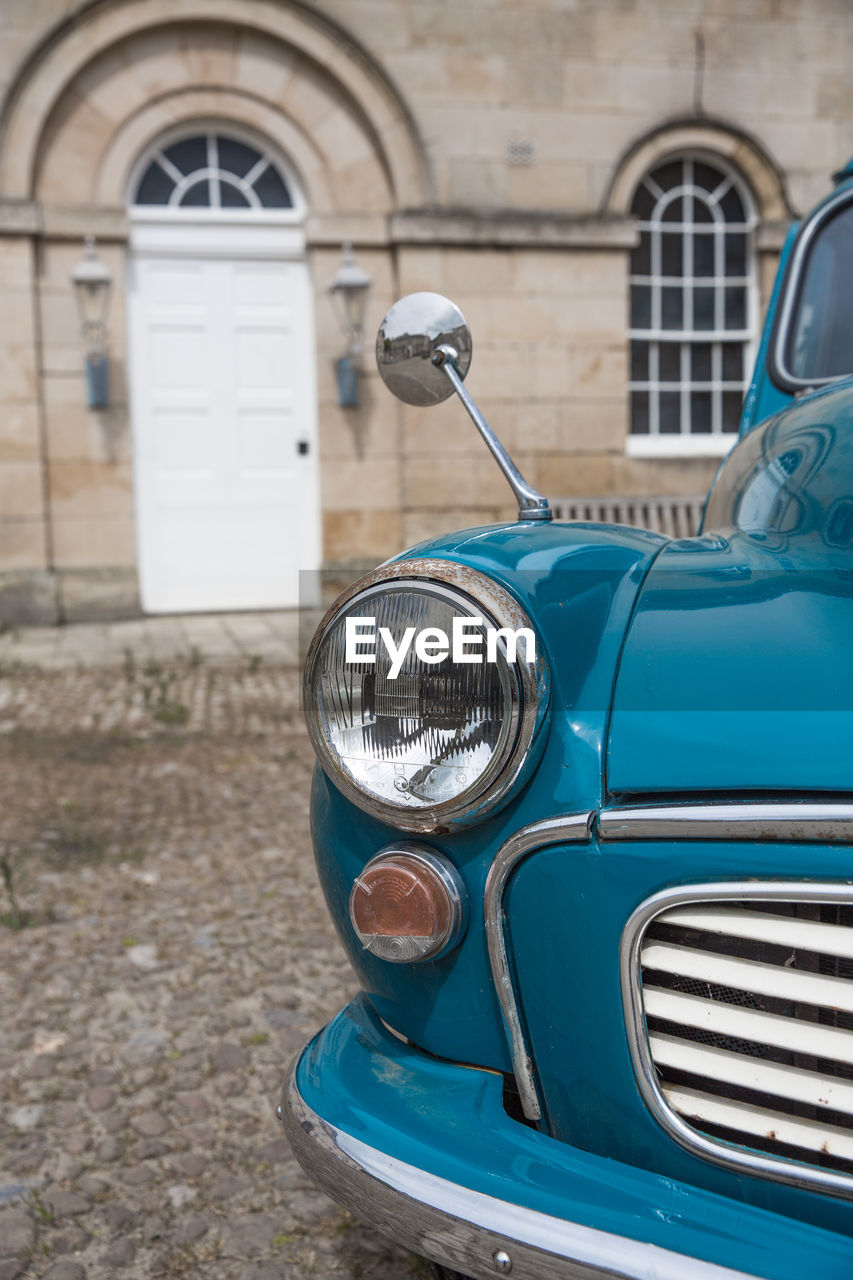 A classic duck egg blue, vintage morris minor car in close up in a luxury lifestyle setting