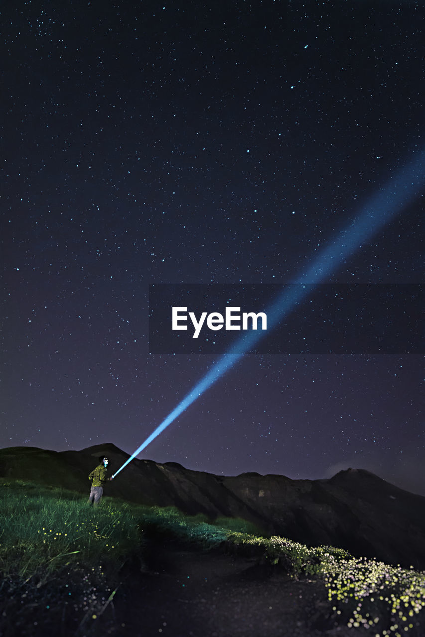 Man With Flashlight Standing On Field Against Sky At Night