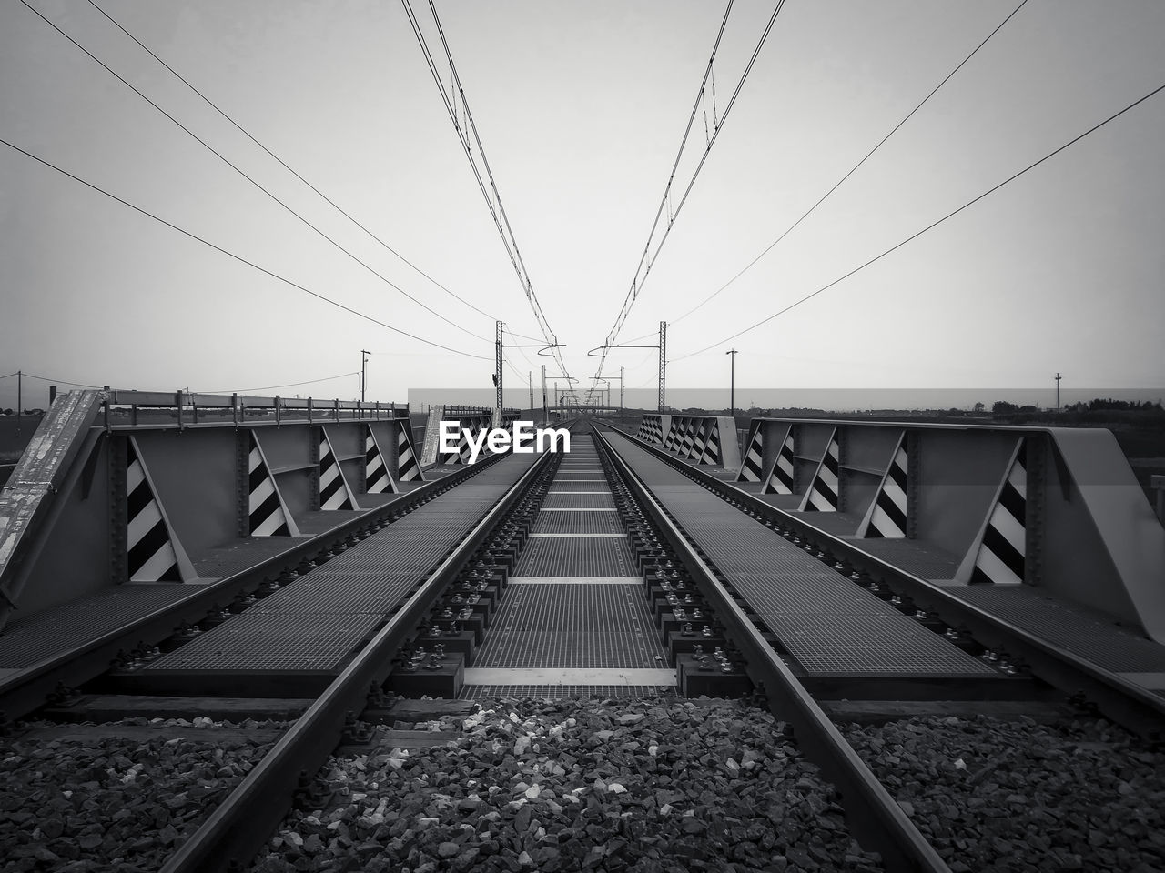 rail transportation, track, transportation, railroad track, diminishing perspective, sky, connection, the way forward, direction, cable, vanishing point, no people, metal, electricity, nature, technology, built structure, architecture, clear sky, power line, straight, parallel, outdoors, long, power supply