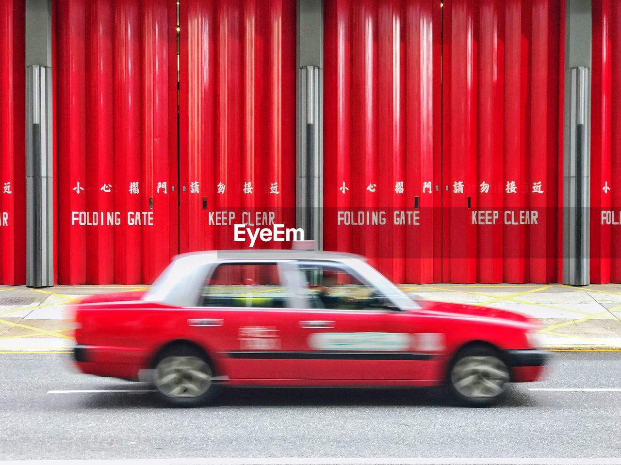 Blurred image of moving taxi against red metallic gate