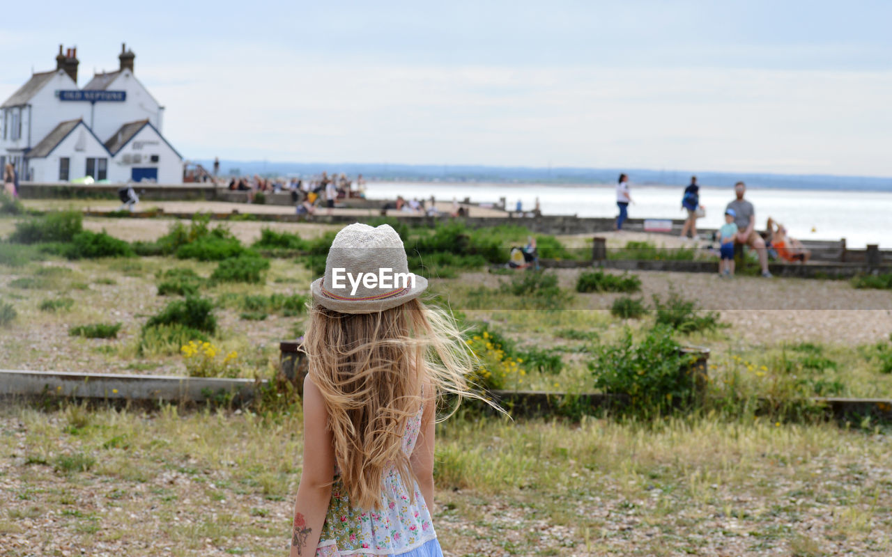 Rear view of girl on grass against sea and sky