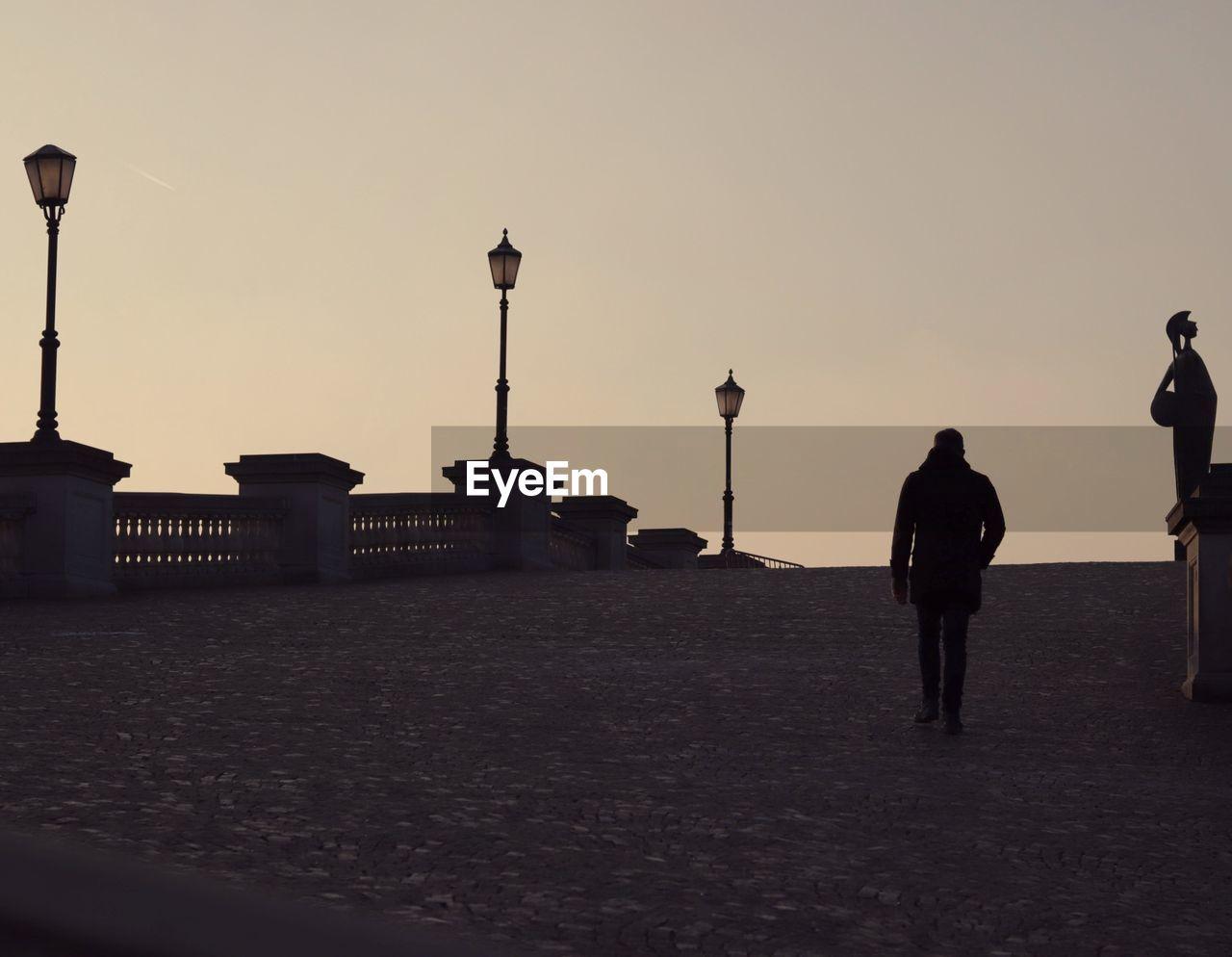 Silhouette Man Walking At Bridge During Sunset
