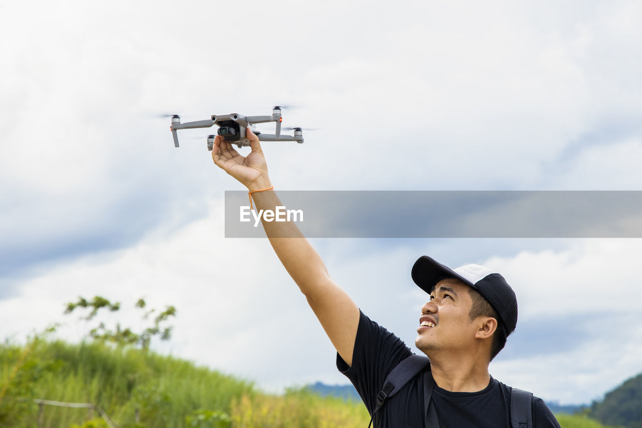 Smiling man holding drone outdoors