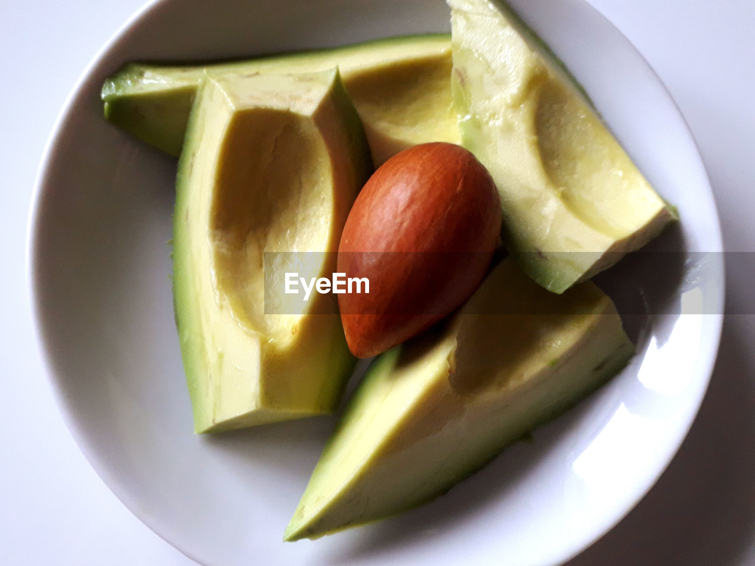 High angle view of avocado slices and seed in bowl on table