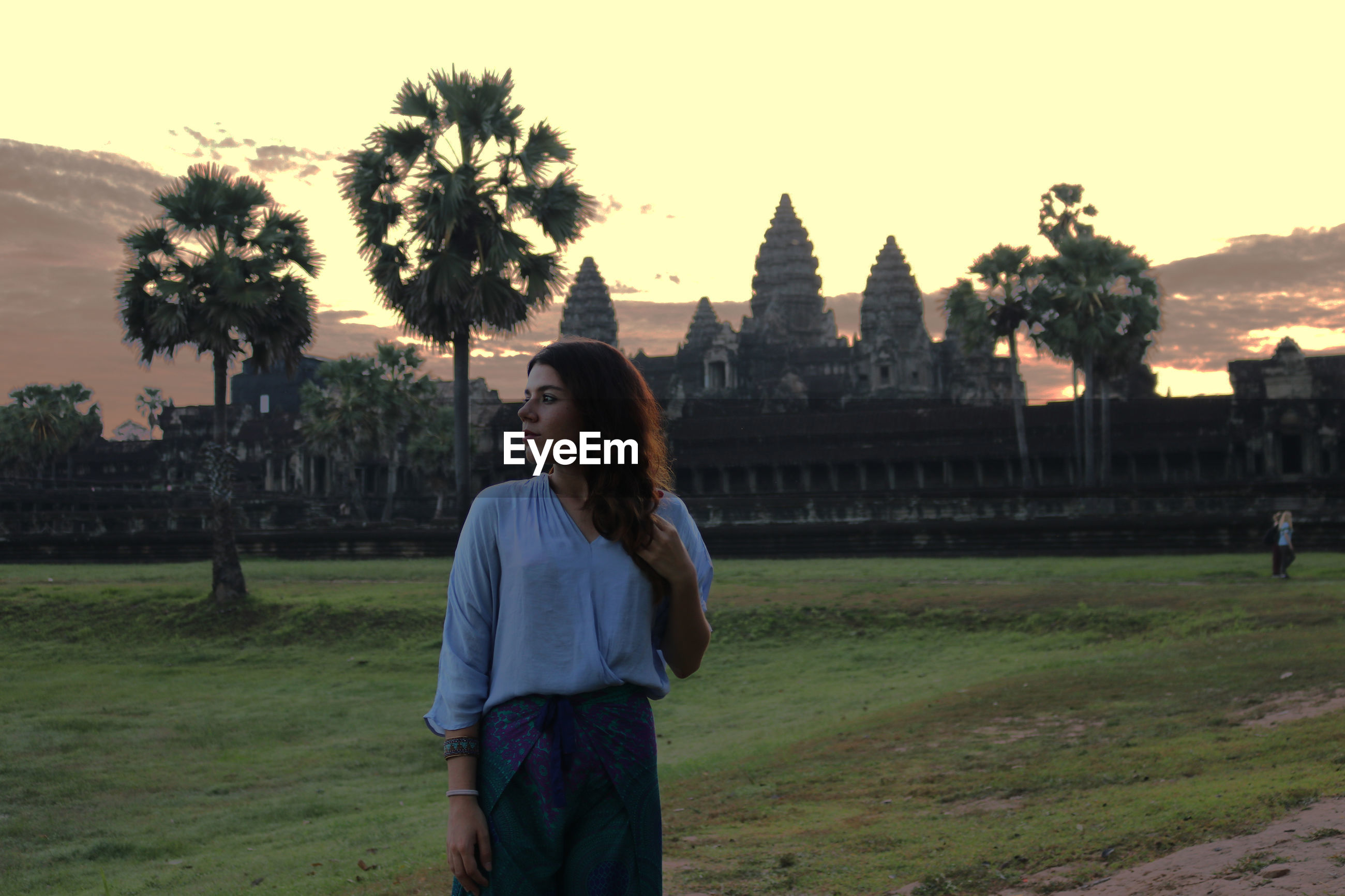 Woman standing against angkor wat temple during sunset