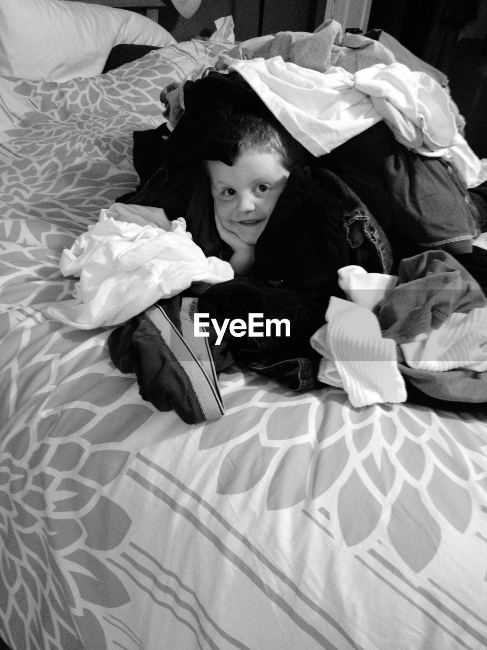 Portrait Of Smiling Boy Covered With Clothes On Bed At Home