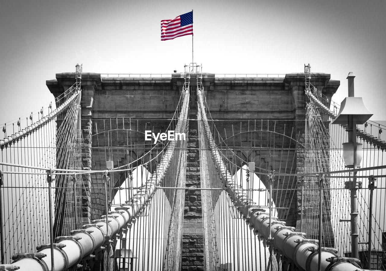 Flag On Brooklyn Bridge Against Sky