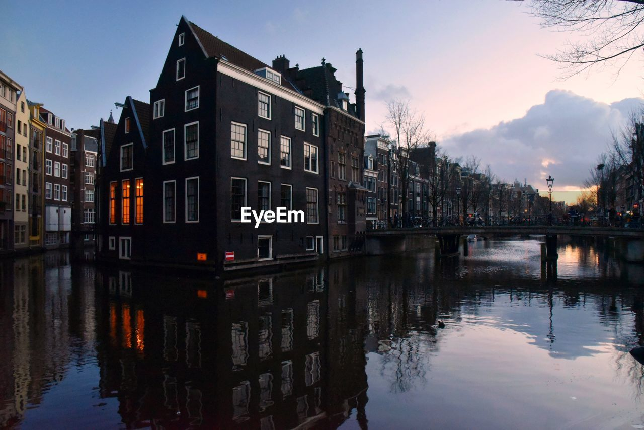building exterior, architecture, water, built structure, reflection, waterfront, sky, building, nature, city, river, residential district, no people, cloud - sky, dusk, outdoors, sunset, transportation, row house