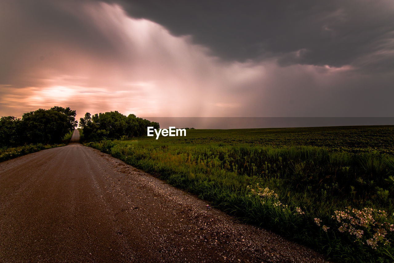 Empty road by field against storm clouds during sunset