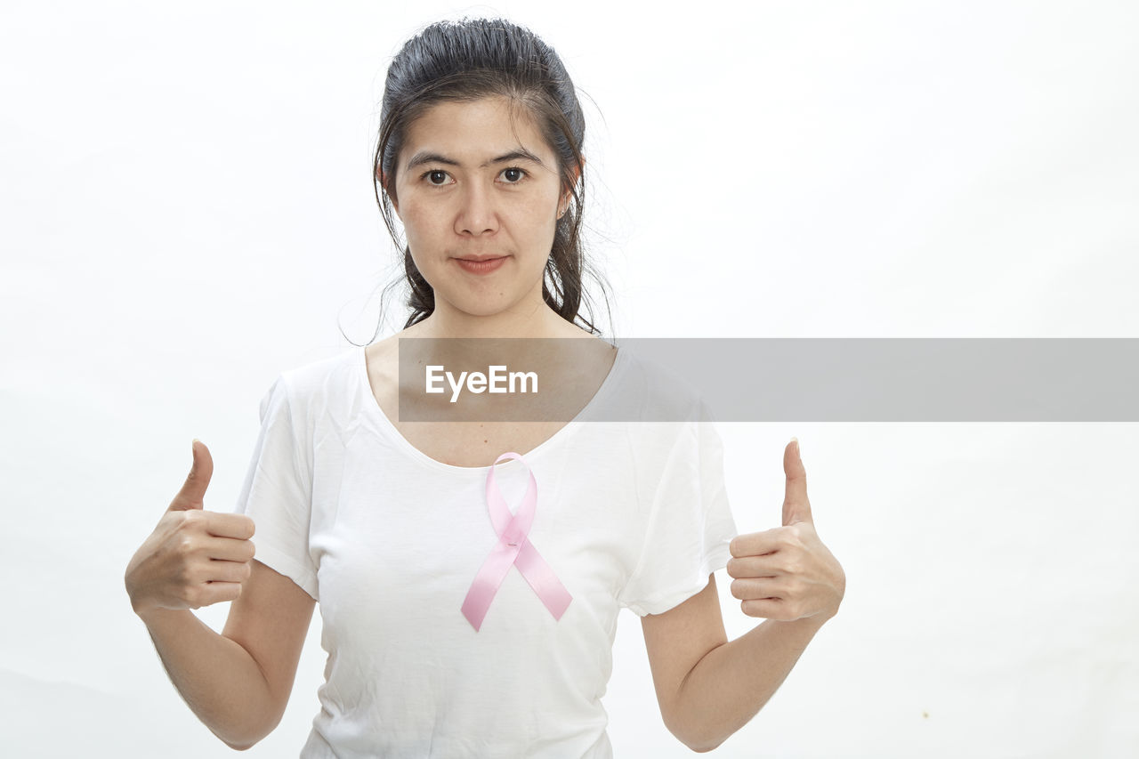 Portrait of woman showing thumbs up while wearing pink ribbon on top against white background
