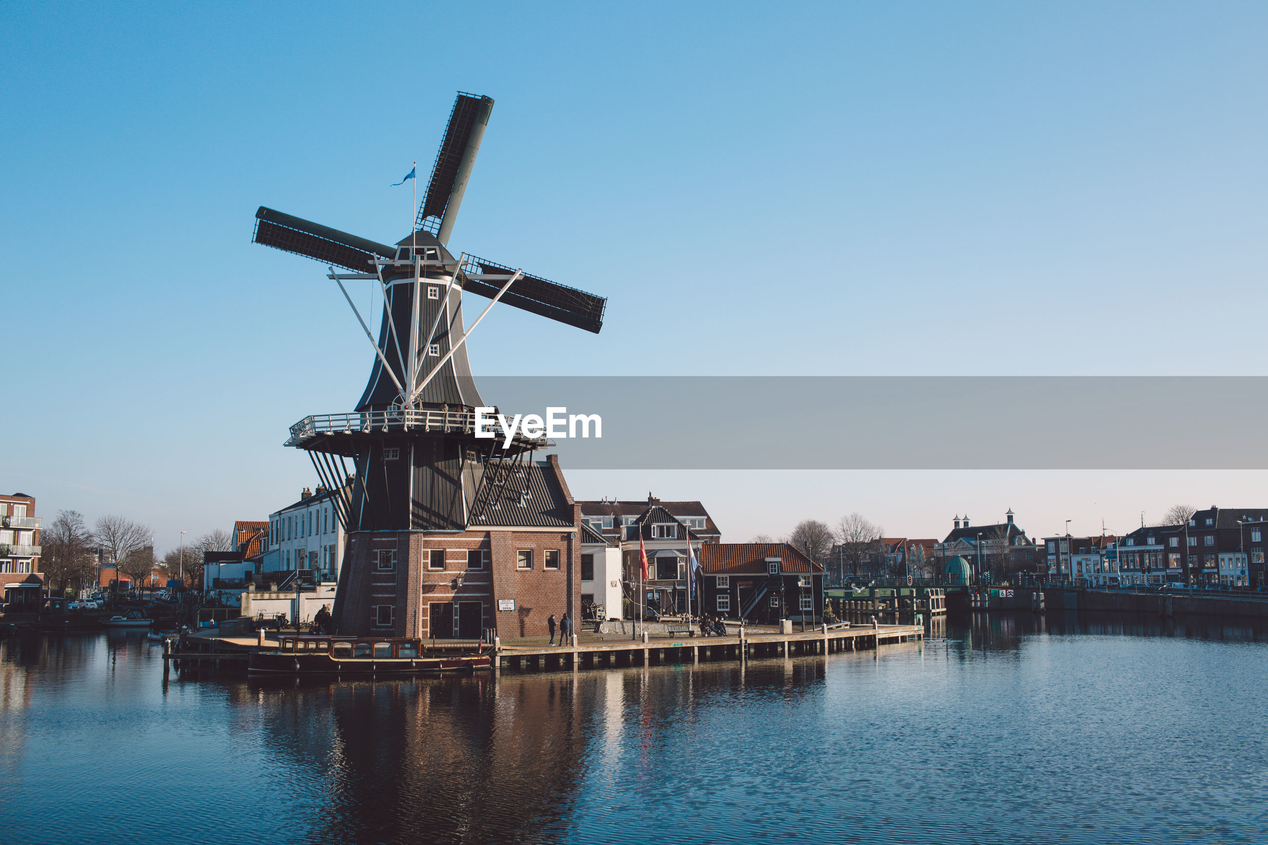 Traditional windmill by river in city