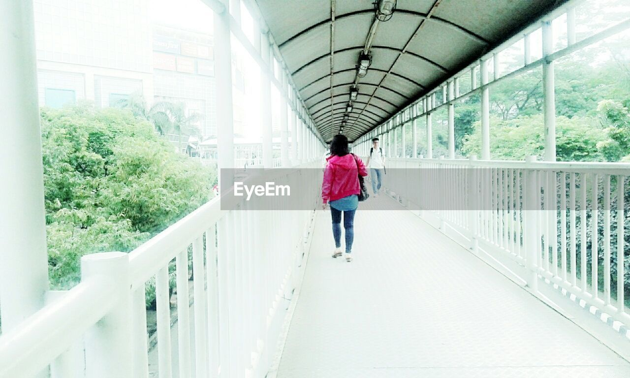 railing, walking, rear view, full length, real people, one person, footbridge, day, architecture, adult, people