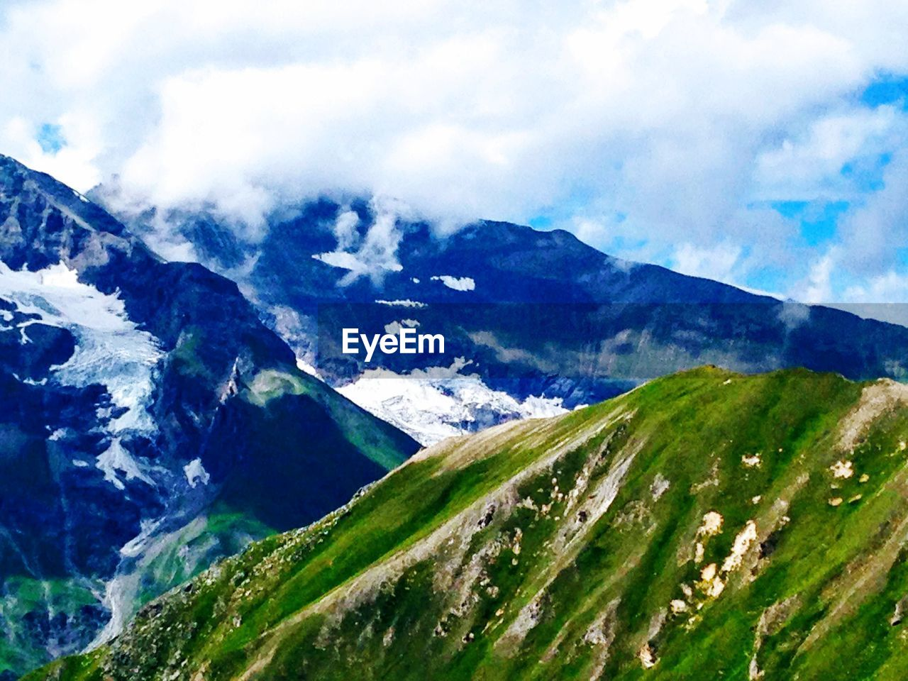 mountain, sky, cloud - sky, beauty in nature, scenics - nature, environment, tranquil scene, landscape, tranquility, nature, no people, day, mountain range, non-urban scene, idyllic, green color, plant, outdoors, land, mountain peak, snowcapped mountain, range