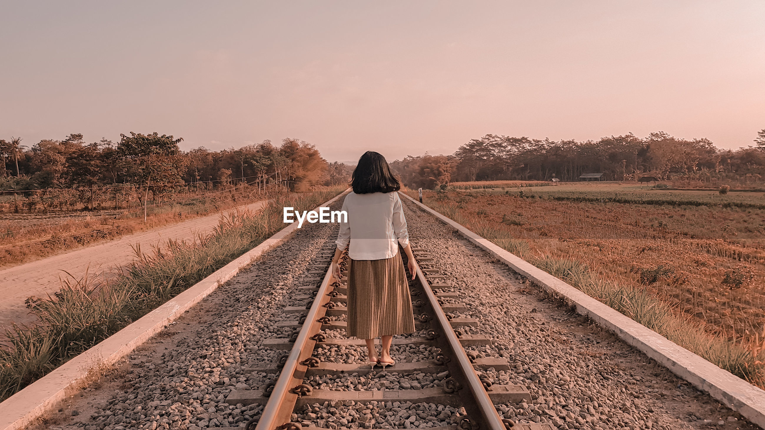 Rear view of woman walking on railroad track against clear sky