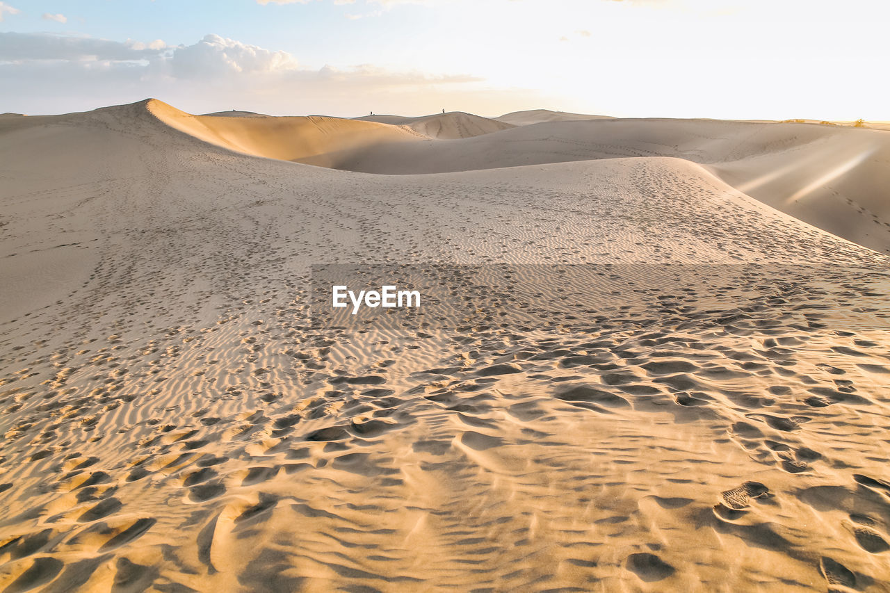 Sand dune with human footprints in desert against sly