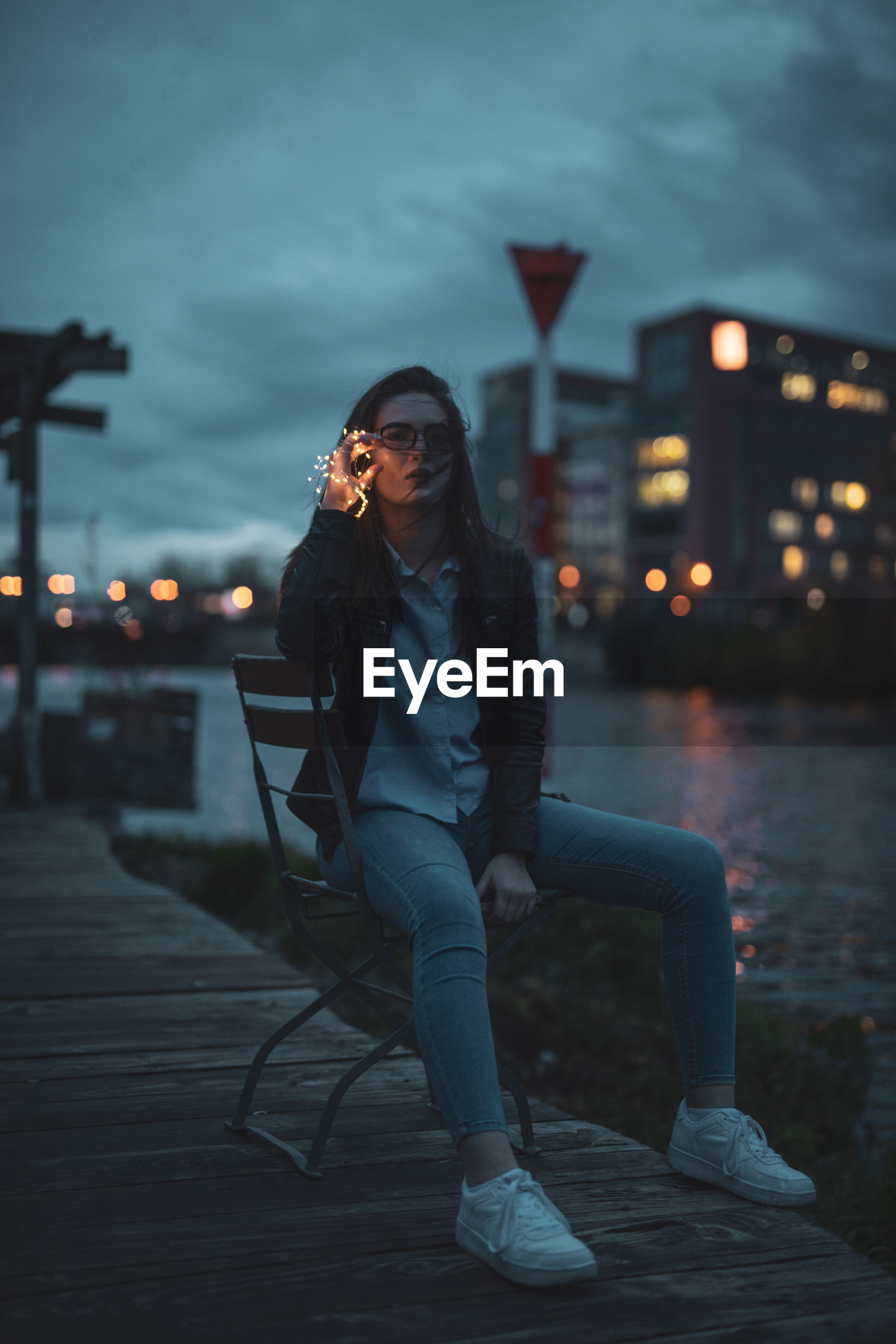 Portrait of young woman sitting on chair at riverbank in city during dusk