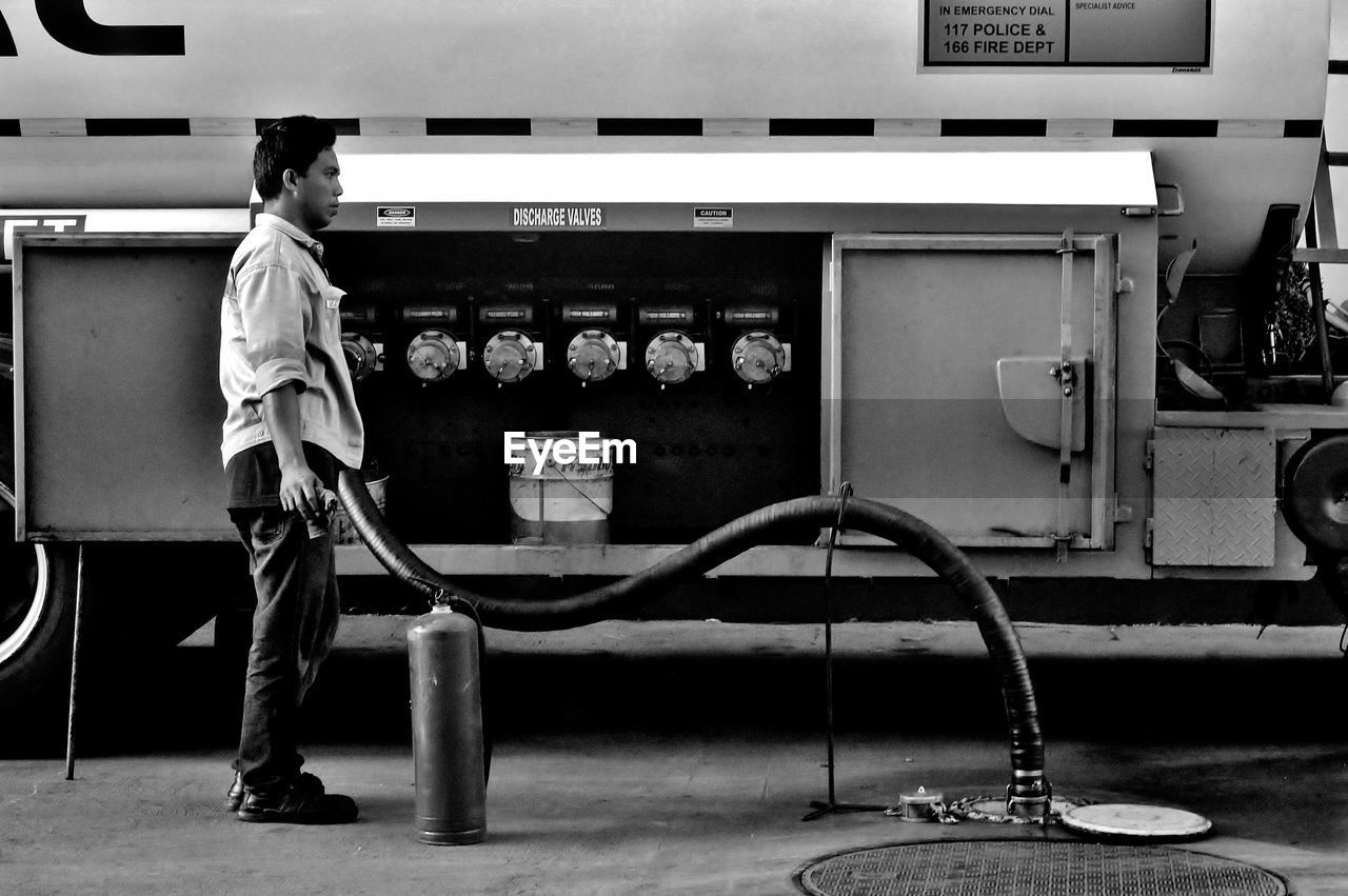real people, one person, casual clothing, full length, standing, fuel and power generation, men, machinery, vending machine, technology, indoors, fuel pump, day, people