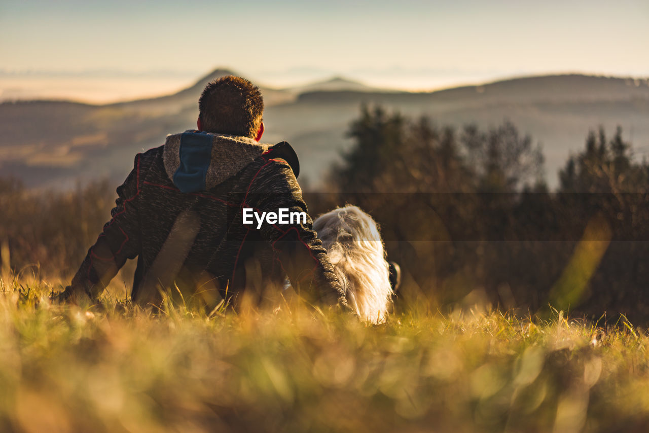 Rear View Of Man With Dog Sitting On Field Against Sky