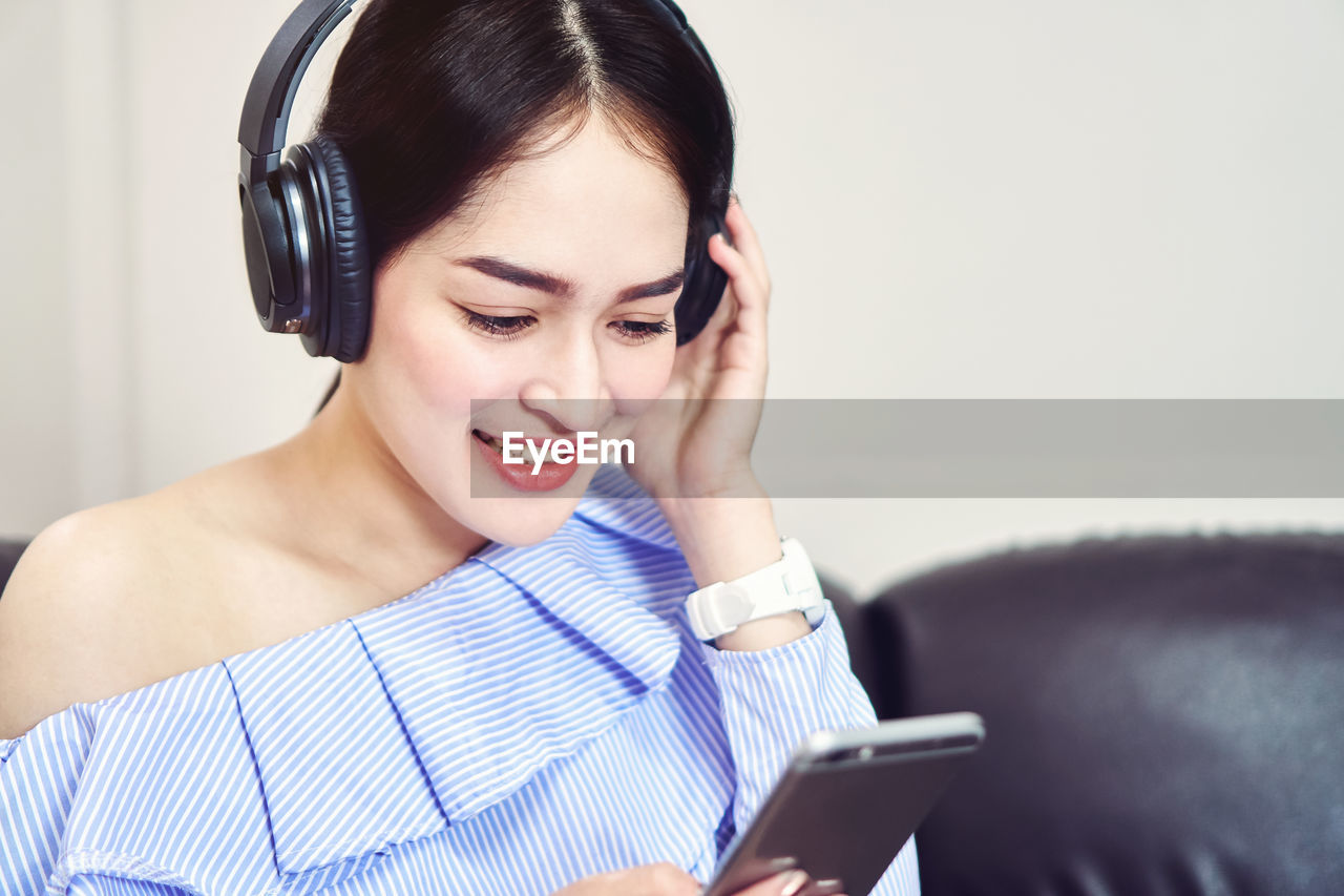 Young Woman Using Phone While Listening To Music At Home
