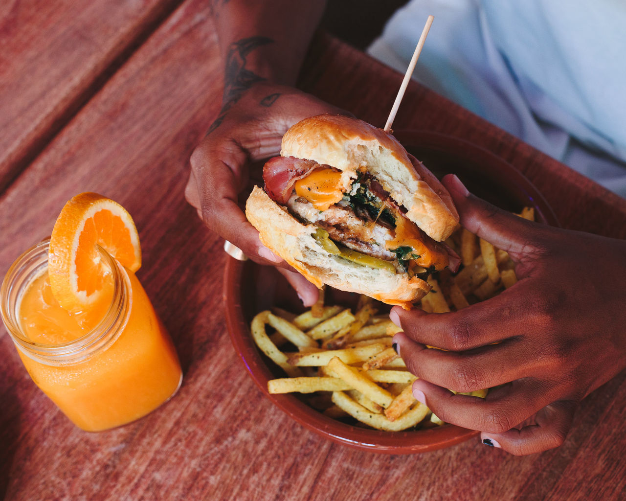 Midsection Of Man Eating Burger At Table