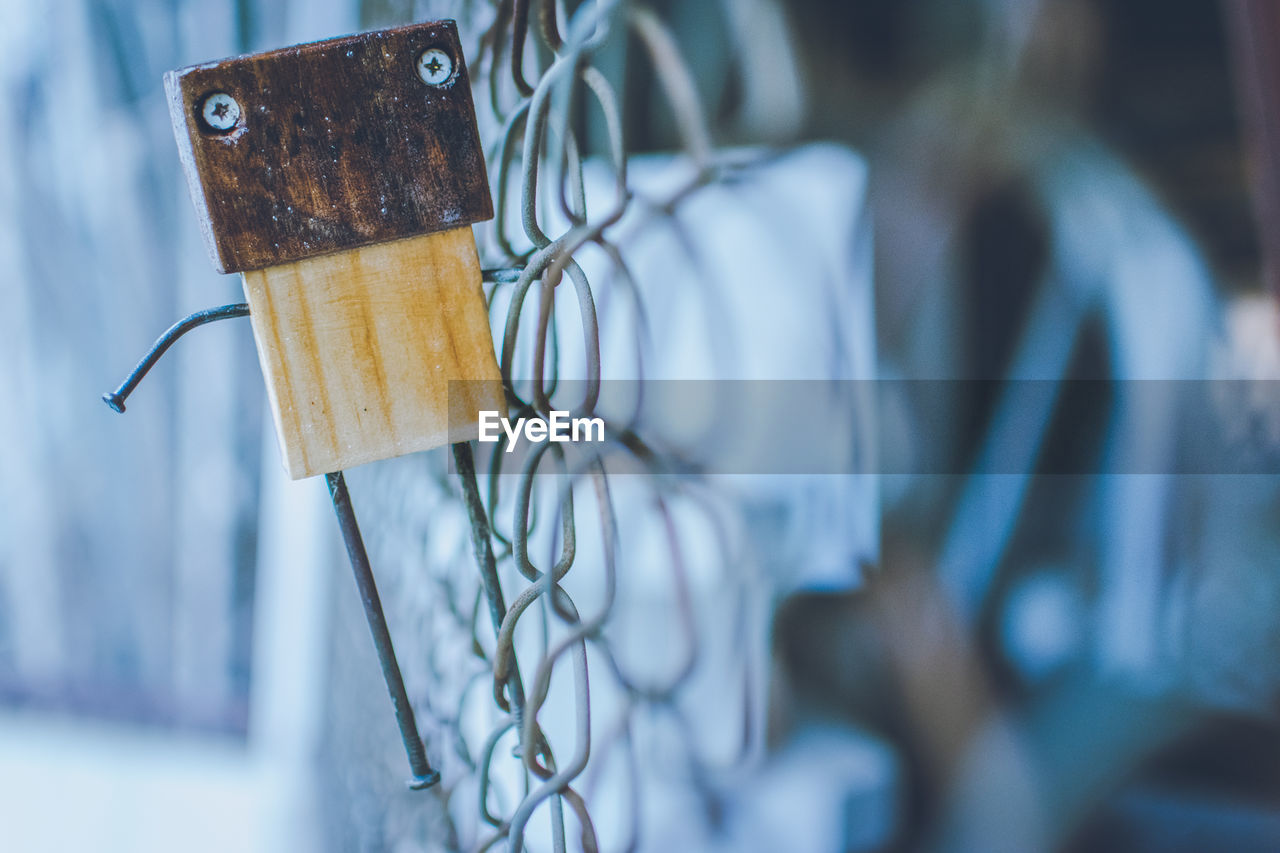 Close-Up Of Figurine Hanging On Chainlink Fence