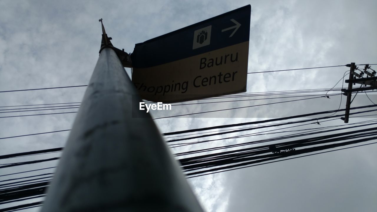 low angle view, sky, cable, communication, outdoors, day, text, cloud - sky, no people, built structure, architecture, close-up