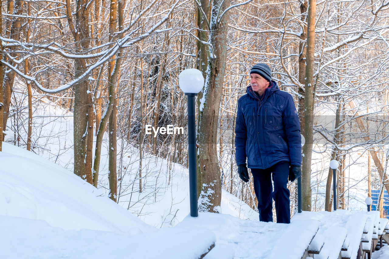 MAN STANDING IN SNOW COVERED LAND