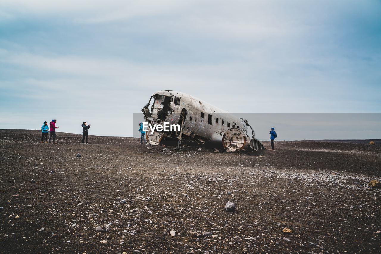 Abandoned airplane on land against sky