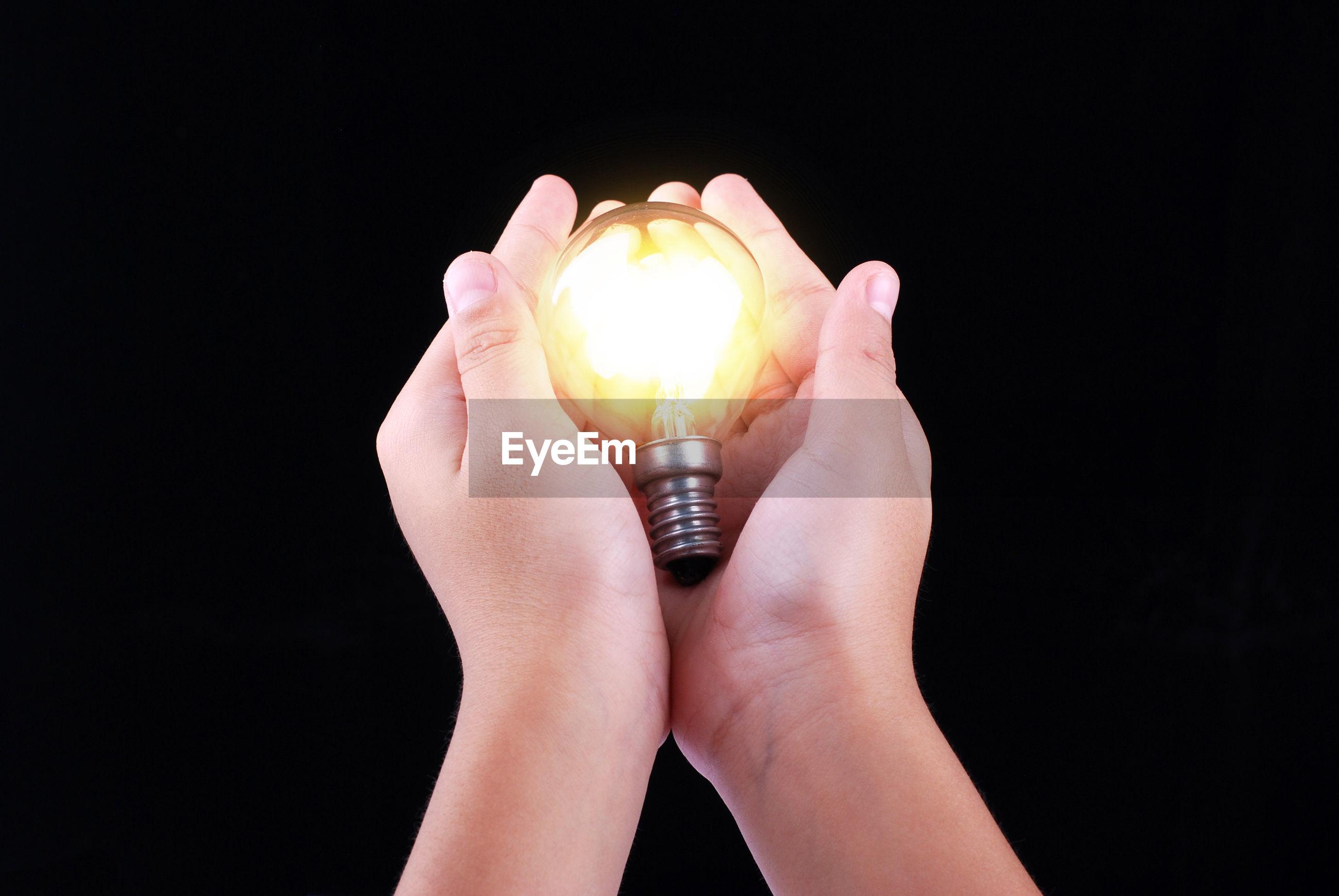 Close-up of hand holding illuminated light bulb against black background