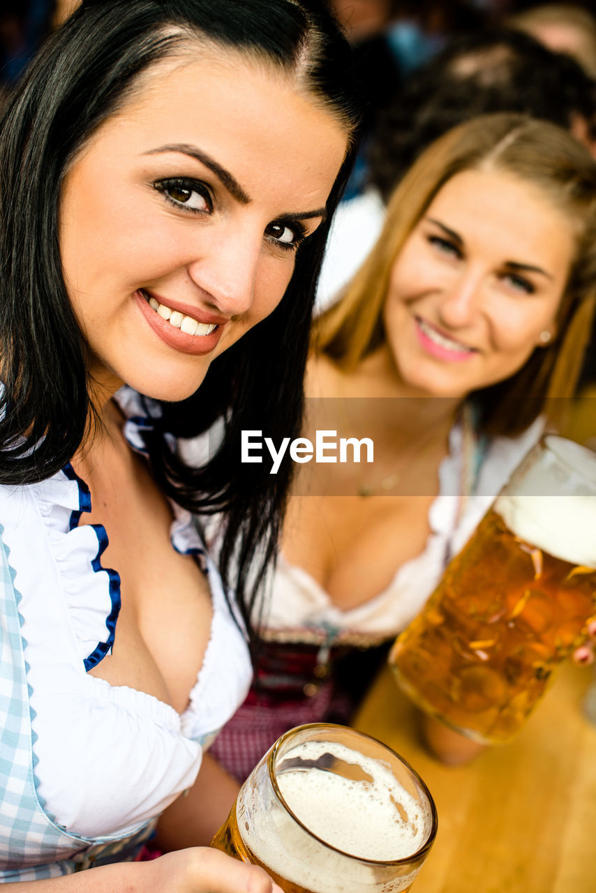 Portrait Of Happy Women Enjoying Beer At Oktoberfest