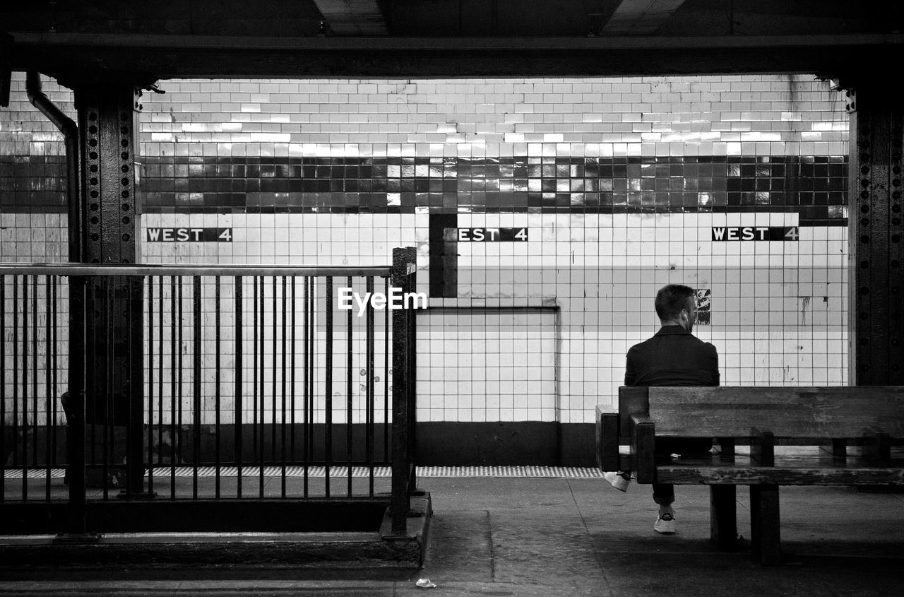 Rear View Of Man Sitting On Bench At Subway Station