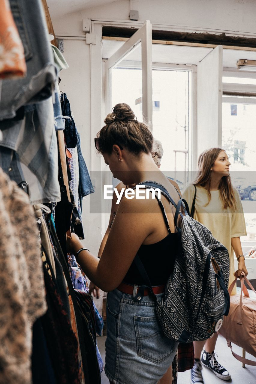 standing, real people, store, shopping, leisure activity, women, people, clothing, indoors, young adult, casual clothing, adult, side view, customer, retail, lifestyles, fashion, choice, two people, getting dressed, decisions, hairstyle, consumerism