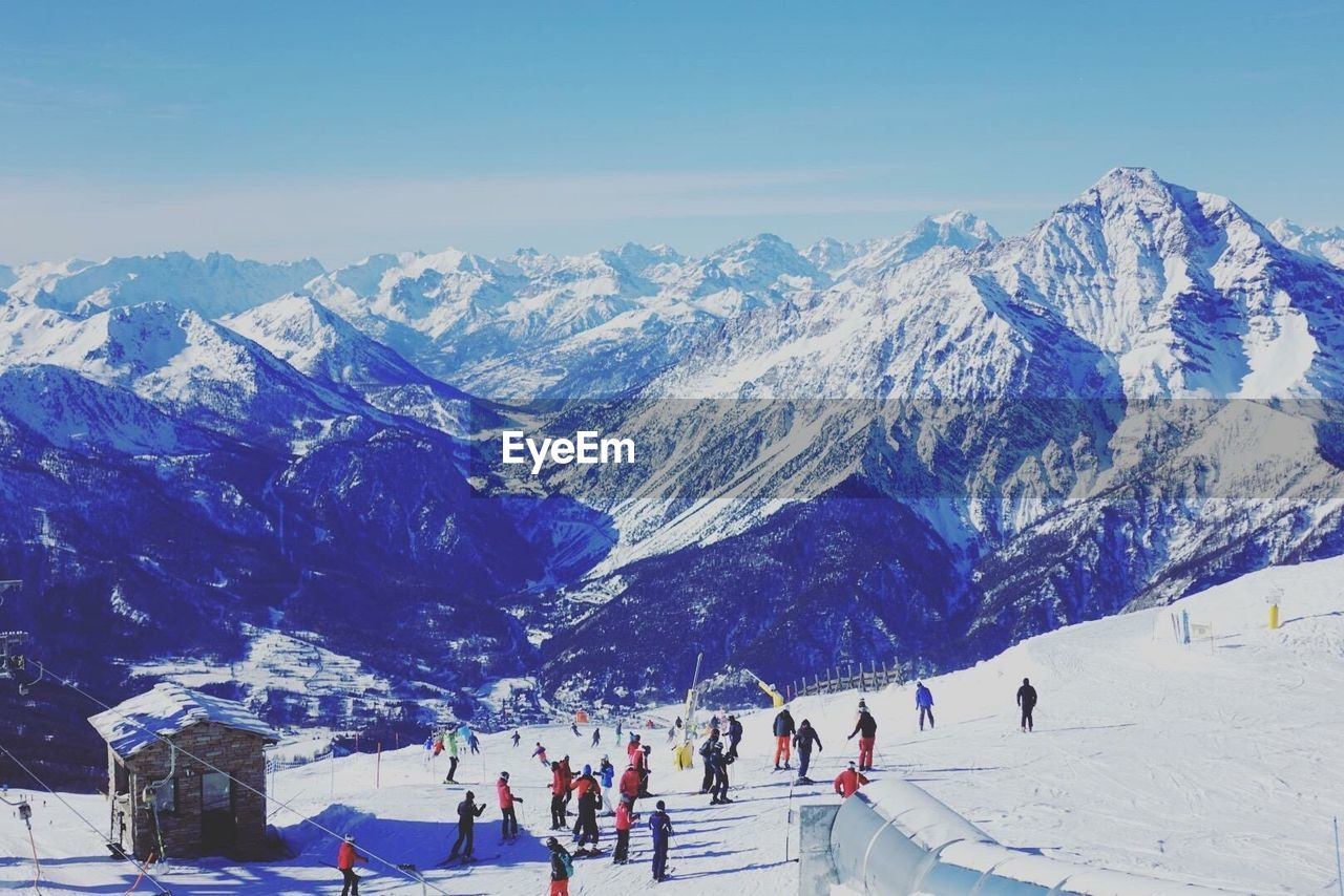 mountain, cold temperature, winter, snow, group of people, mountain range, scenics - nature, real people, leisure activity, beauty in nature, large group of people, sport, crowd, winter sport, lifestyles, snowcapped mountain, nature, men, ski holiday, outdoors