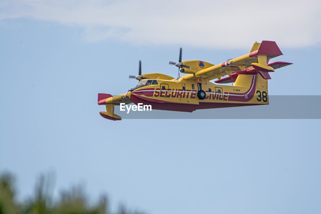 low angle view, transportation, airplane, flying, day, outdoors, no people, sky, air vehicle, clear sky, airshow, nature
