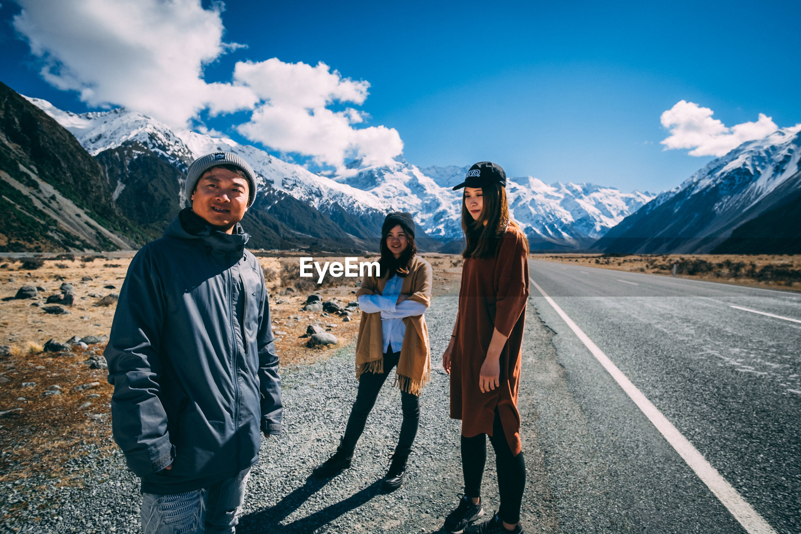FRIENDS STANDING ON ROAD AGAINST MOUNTAINS