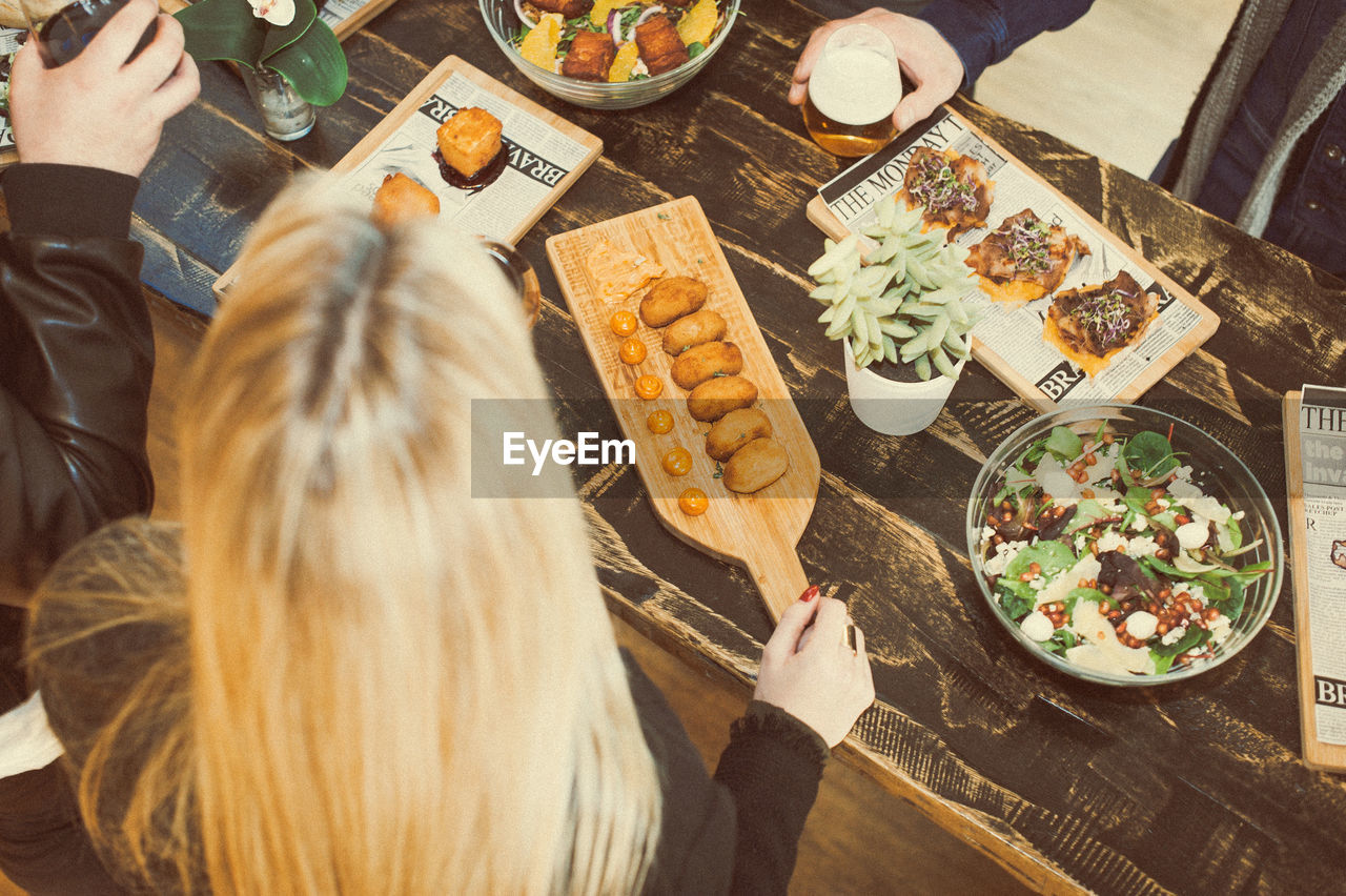 High Angle View Of Friends Having Food At Table In Bar