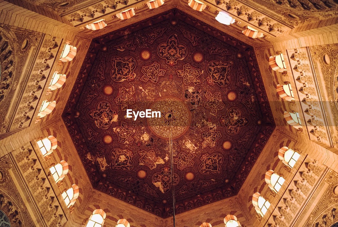 ceiling, indoors, low angle view, architecture, built structure, directly below, travel destinations, no people, pattern, lighting equipment, ornate, religion, history, illuminated, design, art and craft, the past, creativity, shape, dome, cupola, luxury, mural