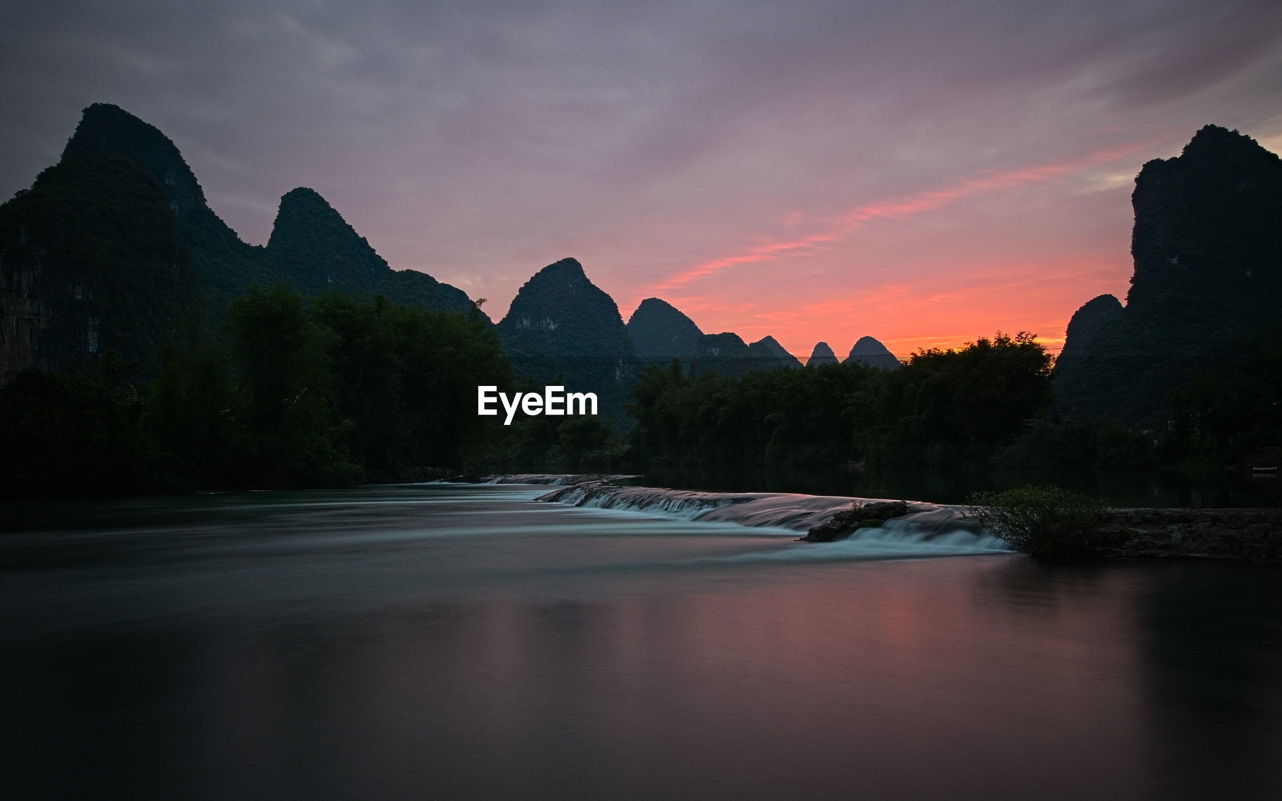 Scenic view of river against sky at sunset