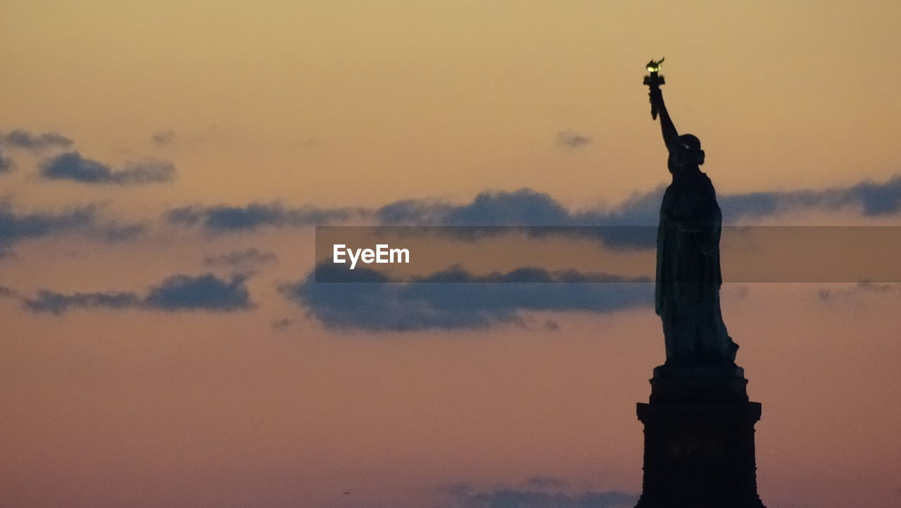 Silhouette statue of liberty against sky during sunset