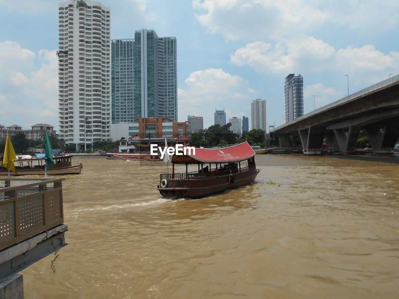 built structure, architecture, building exterior, city, transportation, water, sky, nautical vessel, mode of transportation, waterfront, building, cloud - sky, river, office building exterior, bridge, nature, skyscraper, day, connection, bridge - man made structure, tall - high, no people, outdoors, modern, cityscape, passenger craft