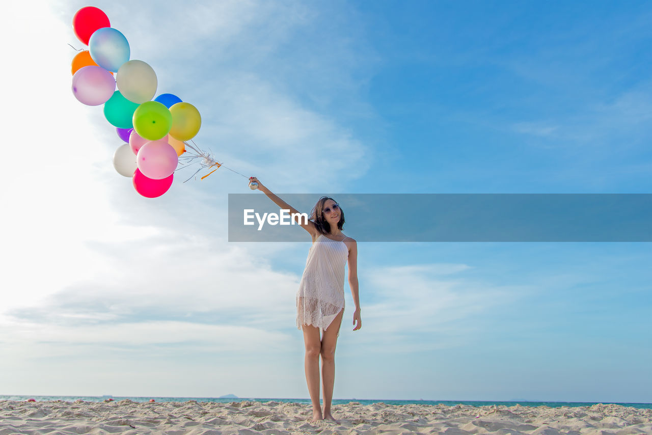 FULL LENGTH OF WOMAN STANDING ON BALLOONS AGAINST SEA