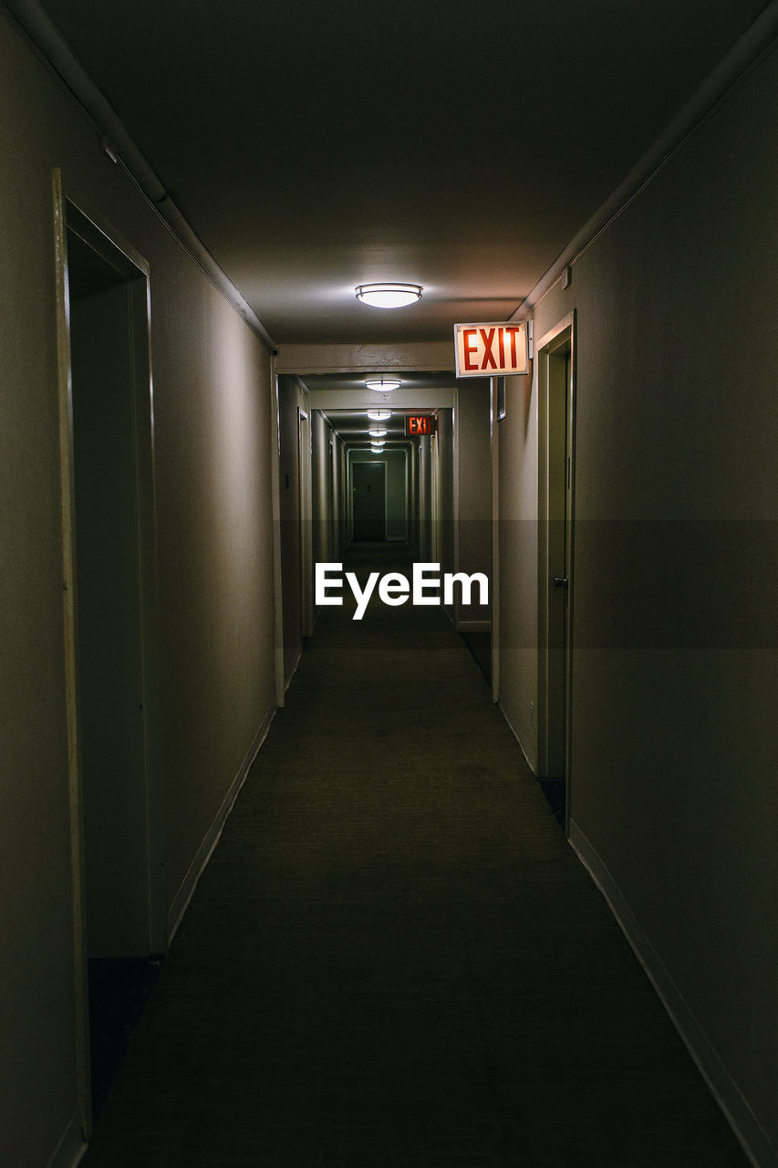 Exit Sign In Illuminated Building Corridor