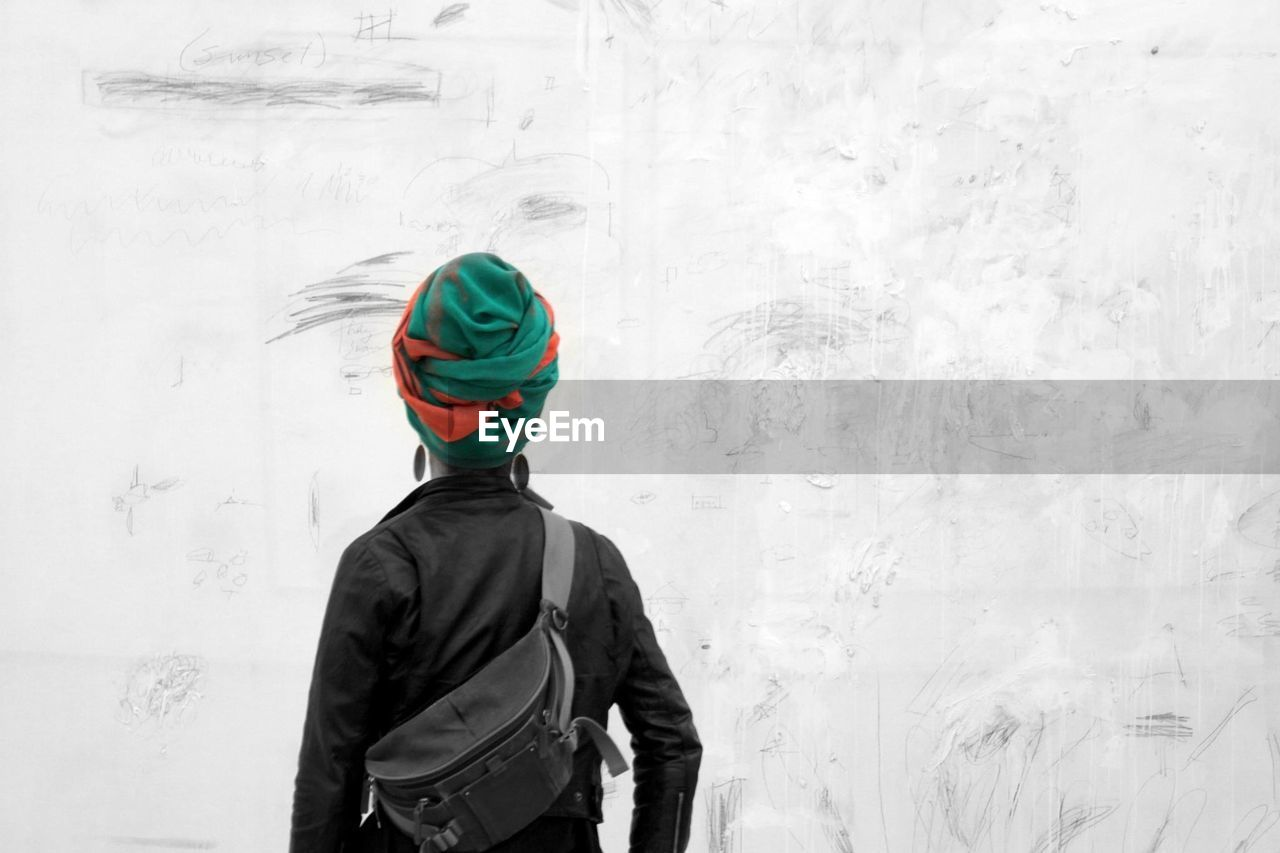 rear view, real people, one person, standing, cold temperature, winter, leisure activity, casual clothing, snow, day, cap, men, outdoors, lifestyles, architecture, warm clothing, headwear, people